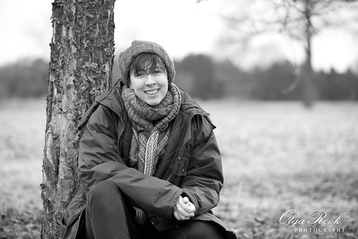 Zwartwit portref van een lachend meisje in een tuin in de winter.
