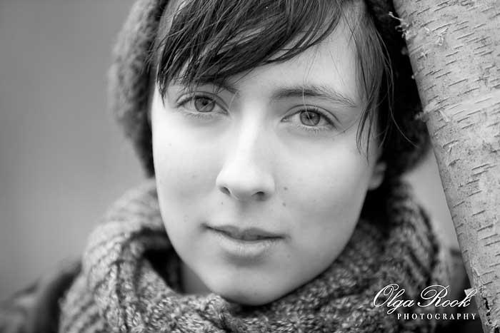 Zwartwit portret van een mooi meisje: ze draag winterkleren en leunt tegen een berk.