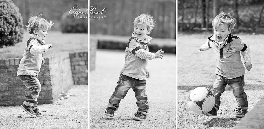 Klein vrolijk jongentje aan het springen, dansen en voetballen in een park.