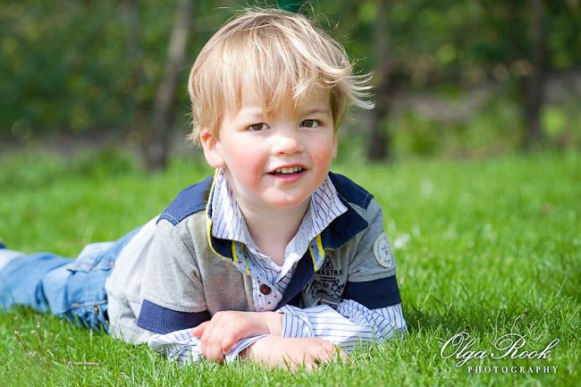 Portret van een jongentje liggend in het gras.