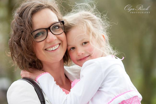 Portret van een moeder die haar dochterje in haar armen houdt: teder, dromerig en natuurlijk.