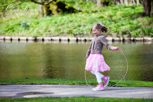 Klein meisje springt touwtje in een park.