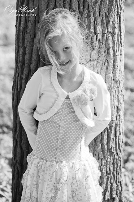 Zwartwit portret van een verlegen blond meisje in een park.