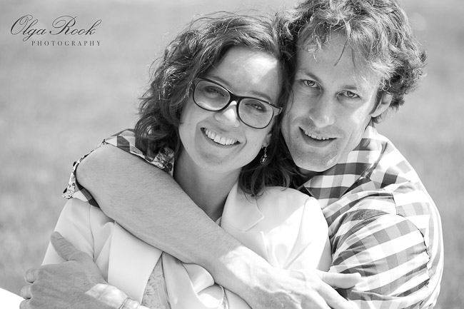 Black and white portrait of a couple lying in the grass in a park.