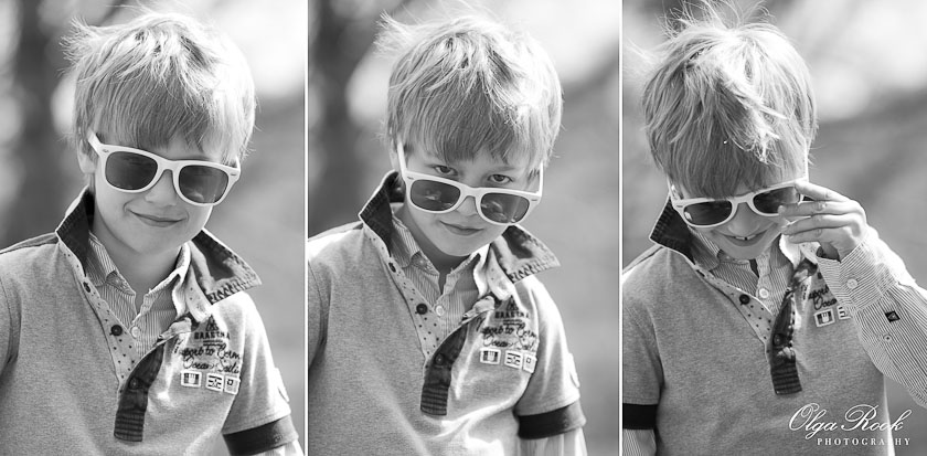 Portrait of a boy wearing sunglasses: he tries to look tough but then laughs again.
