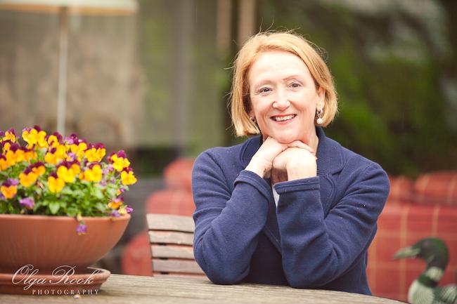 Portret van een dame zittend bij haar in de tuin.