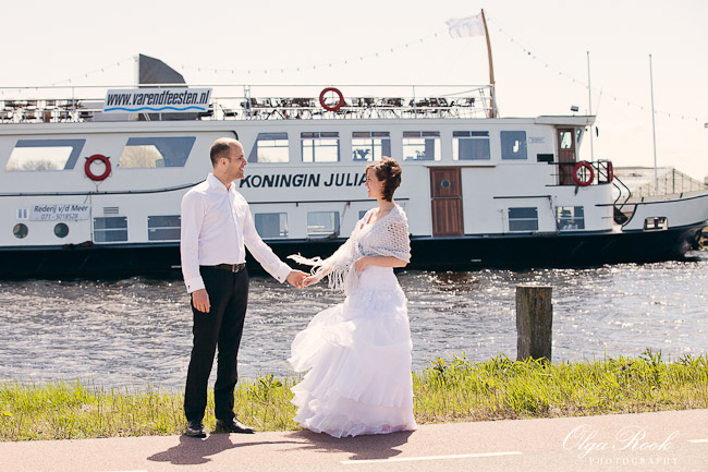 A bride and groom on a river bank with a boat behind them.