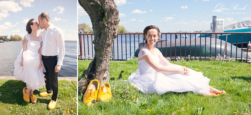 Bride and groom wearing Dutch wooden shoes on a river bank.
