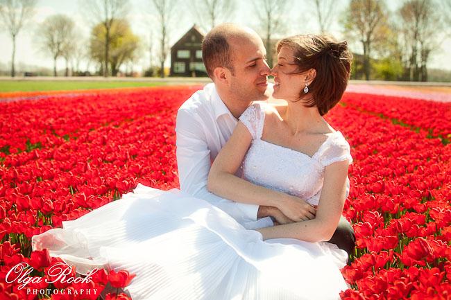 Een bruidspaar dat in het midden van een veld met vuurrode tulpen zit.