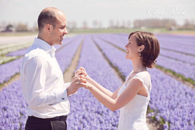 De bruidegom en de bruid houden elkaar's handen voor een bloemenveld met lila bloemen.