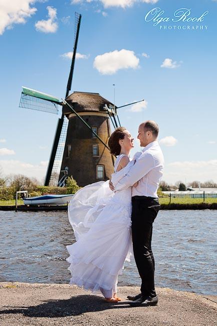 Een romantisch bruidspaar met een windmolen in het achtergrond.
