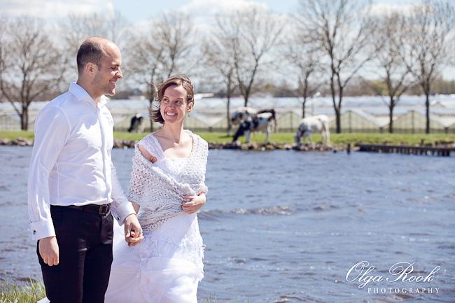 Romantische stel wandelt bij de rivier: op het achtergrond lopen koeien en zijn glashuizen te zien.