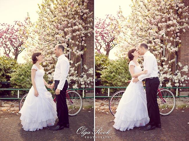 Foto van een bruidspaar met een fits tussen de bloeiende bomen.