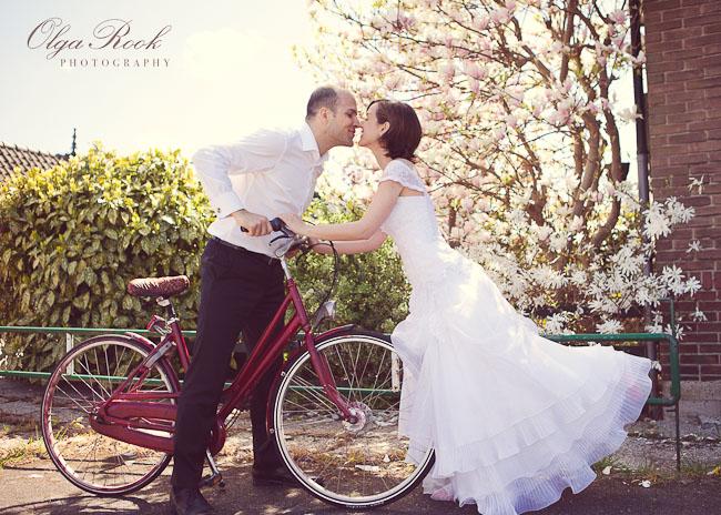 Een romantische foto van een zoenend bruidspaar met een fiets.