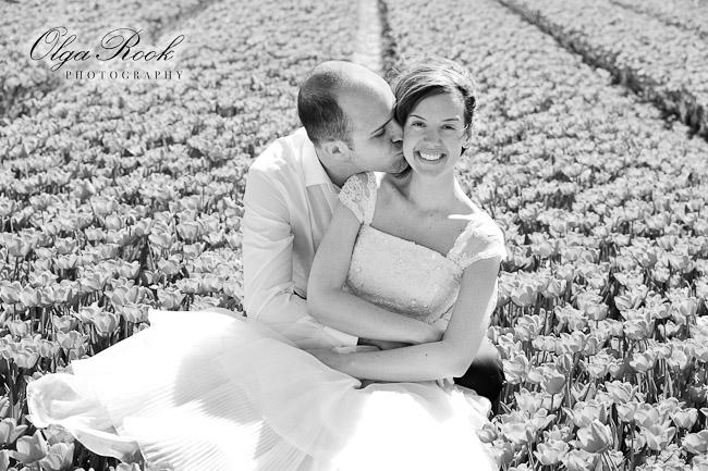 Klassiek zwarwit foto van een bruidspaar in het midden van een bloemenveld.