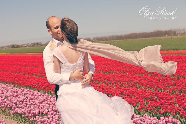 Een bruidspaar in een tulpenveld op een prachtige zonnige dag.