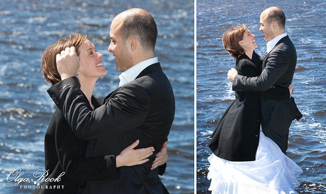 Portret van een bruidspaar naast een rivier: ze omhelzen elkaar en lachen vol geluk.