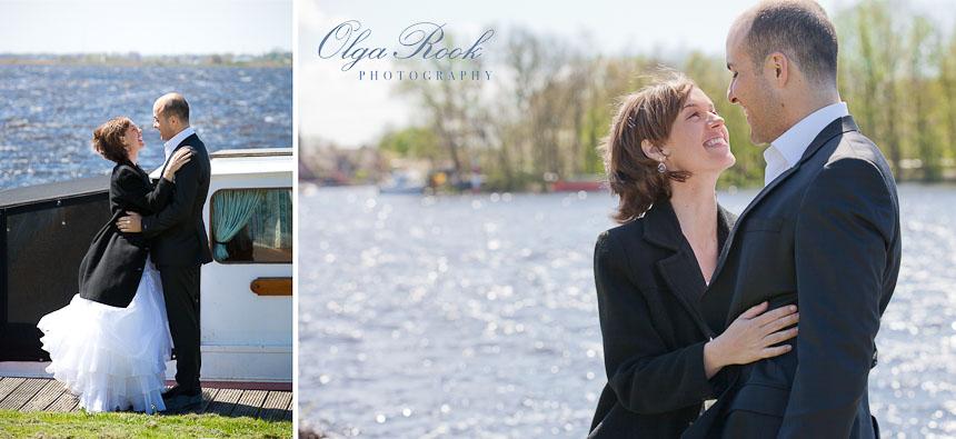 Een bruidspaar staat naast een boot bij de rivier.