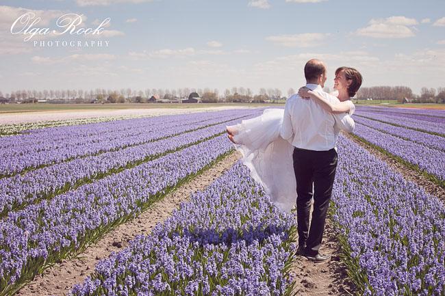 Romantische bruiloftsfoto in pasteltinten: de bruidegom houdt de bruid in zijn armen in het midden van een hyacintenveld.