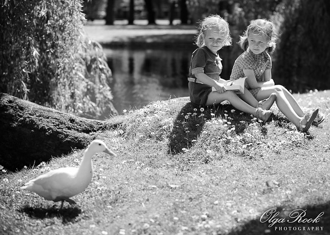 Classic black and white photo of two little girls sitting on the river bank with a book. They look how a white duck passes them by.