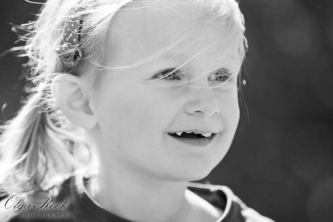Black and white portrait of a two-year old girl laughing.