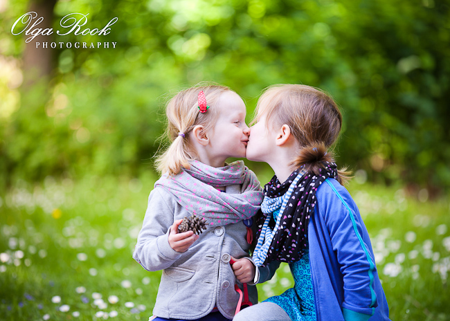 Color photo of two little sisters giving each other a kiss.