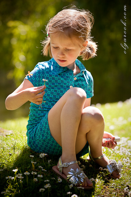 Dreamy portrait of a little girl in a park looking at a daisy she had just plucked.
