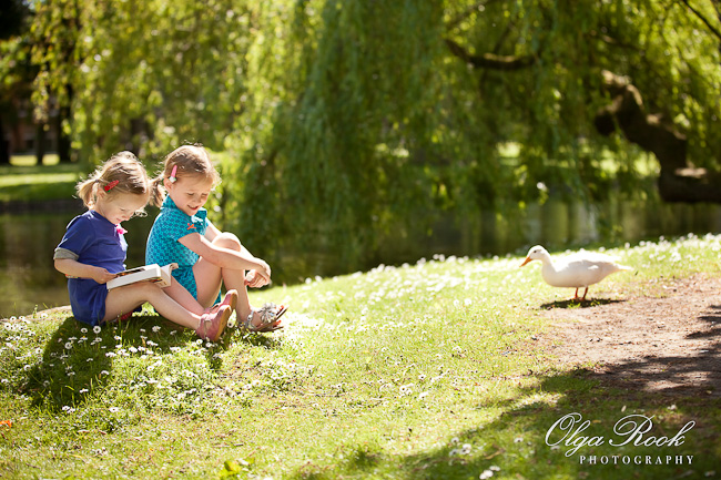 Color photo of two little girls sitting in the grass with a book on a sunny day. There is a duck walking next to them. The photo conveys the atmosphere of joy and serenity.