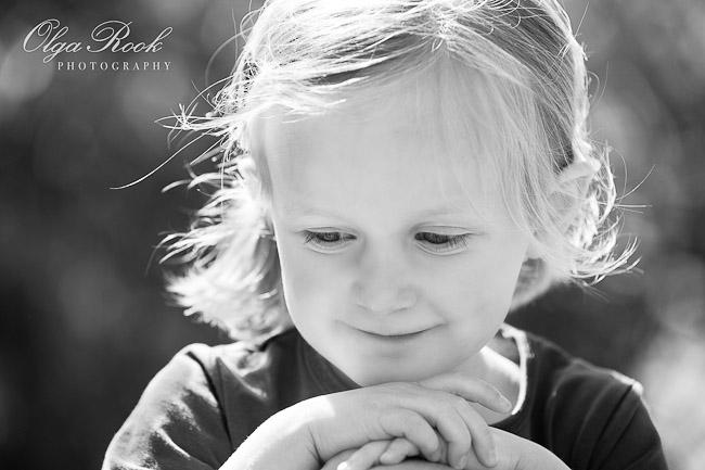 Zwartwit portret van een tweejarig meisje met een zacht en dromerig glimlach.