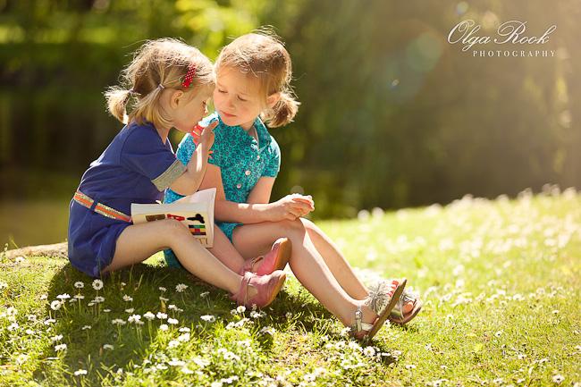 Foto van twee kleine meisjes in het gras op een zonnige dag: dromerig en idyllisch.