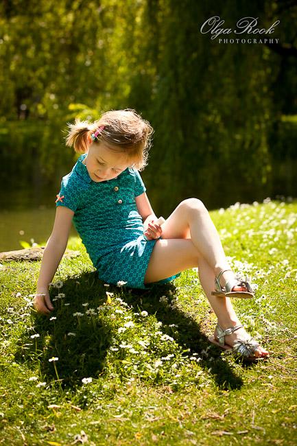 Foto van een klein meisje die een madeliefje in een park plukt.