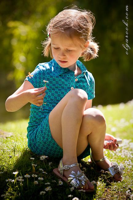 Portret van een klein meisje met een madeliefje die ze net heeft geplukt.