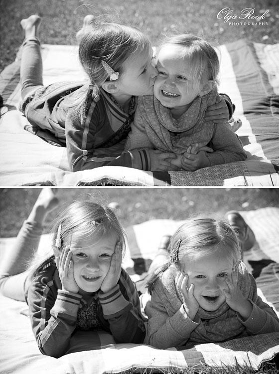 Zwartwit foto van twee kleine meisjes: ze liggen op een picknickkleed in een park op een zonnige dag en hebben grappige gezichtsuitdrukkingen.