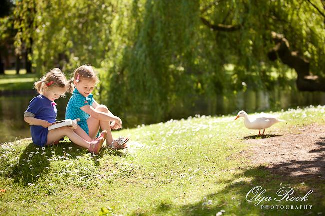 Dromerige kleurenfoto van twee kleine meisjes die in een park in het gras met een boekje zitten.