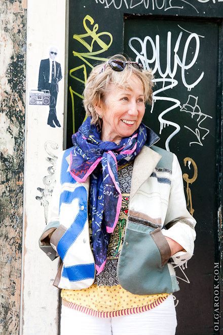 Portrait of an elegant middle aged lady standing against a wall covered with colorful grafitti.