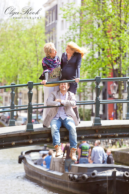Funny family photograph on a bridge in Amsterdam: a young man is sitting on a bridge and his mother and girlfriend are standing above him.