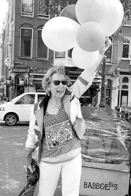 Photo of an elegantly dressed lady holding a bundle of balloons in a street of Amsterdam.