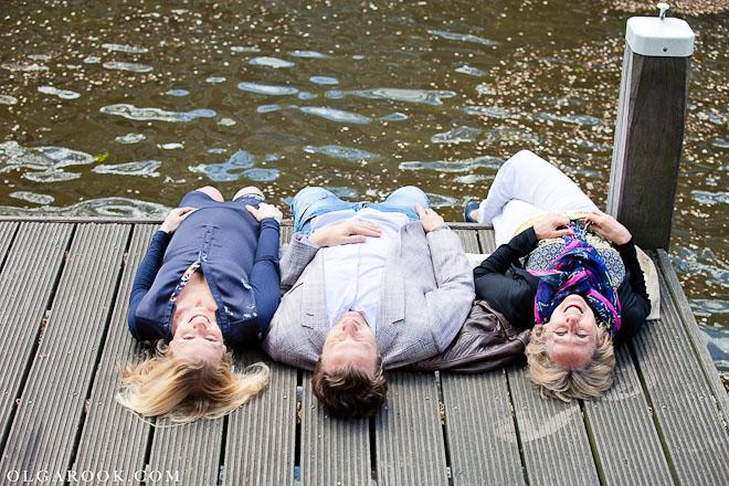 Foto van een familie liggend in de zon op een boot kade in Amsterdam.