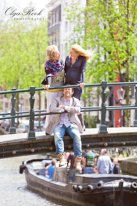 Grappige familiefoto: een jonge man zit op een brug, en zijn moeder en vriendin staan boven hem.