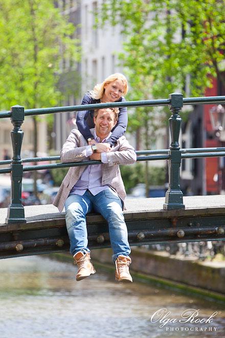 Portret van een lachende paar op een brug in Amsterdam op een zonnige dag.