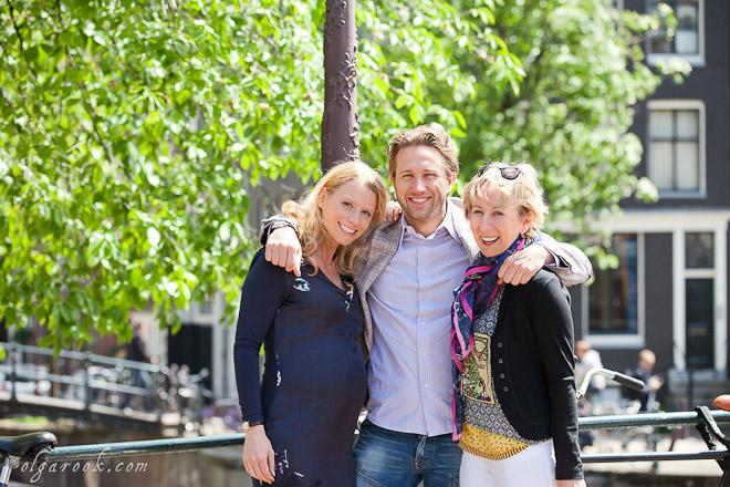 Familieportret op een straat van Amsterdam: een jonge man omhelst zijn vriendin en zijn moeder.