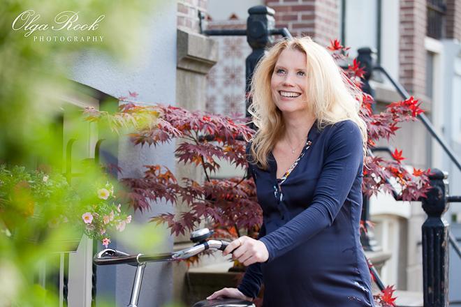 Kleurenportret van een mooie blonde vrouw met fiets op een staat van Amsterdam.