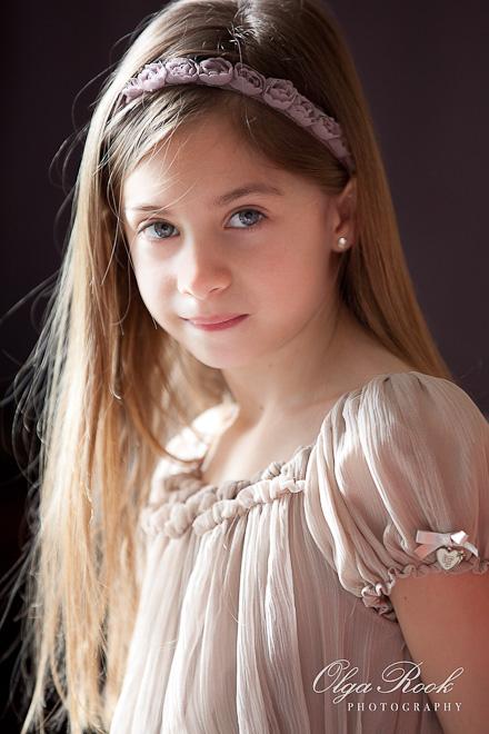 Een schilderachtige fotoportret van een klein mooie meisje met lange haren en een mooi jurk.
