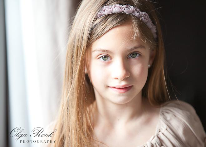 Charmante portret van een klein meisje voor het raam. Zij is lief, heeft lange blonde haar en draagt een mooi jurkje. Deze foto heeft een retro uitstraling.