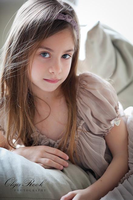 Foto van een klein meisje met lange haren. Zij draagt een mooie chiffonjurk in zachte pastelkleur. Het portret heeft een retro of zelfs baroque esthetiek.