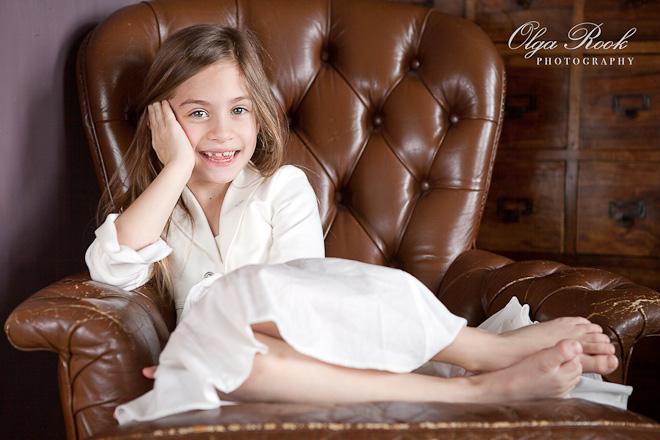Foto van een klein lachend meisje, die ontspannen in een grote antieke leunstoel zit.