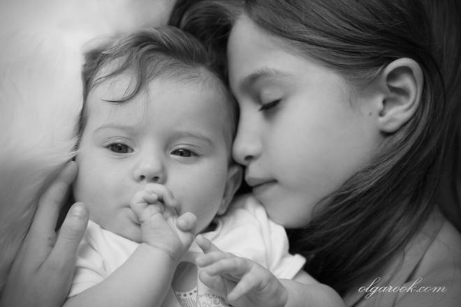 Nostalgisch portret van twee zusjes. De oudere meisje slaapt en houdt haar baby-zus in haar armen, terwijl de baby een mediterend blikje heeft.
