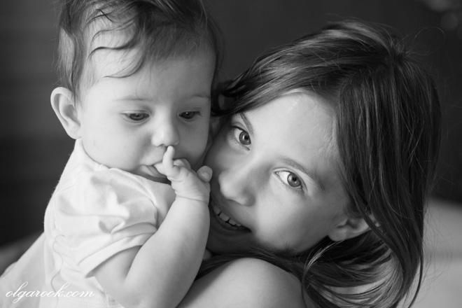 Nostalgische foto van twe zusjes: de oudste houdt haar jongere zus in haar handen.