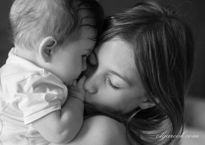Zwart-witte foto van twee zusjes. Het beeld is vol emotie: men kan de liefde van de oudere zus voor haar kleine zusje voelen.