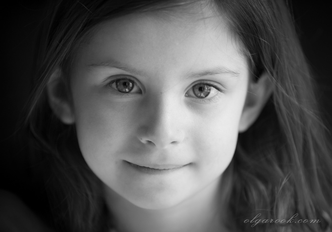 Black and white portrait of a little girl: her look is attentive, confident and intelligent.